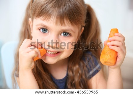 Little girl with carrot, close up