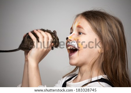 little girl with cat painting on her face catching a mouse. - stock photo