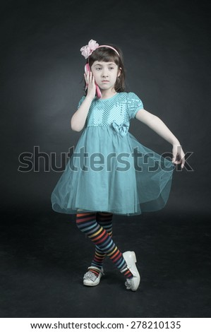 Little girl with cell phone on dark background - stock photo