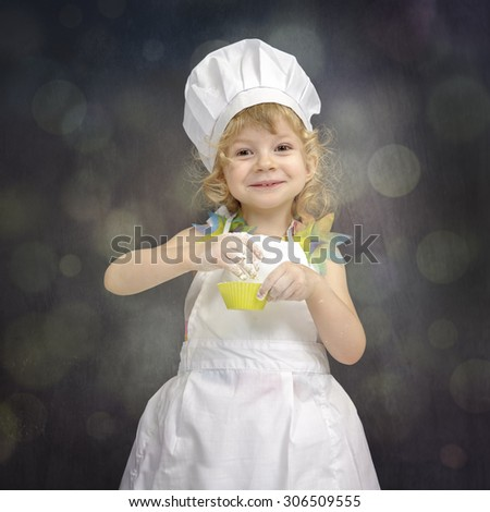 little girl with chef hat,making cup cakes