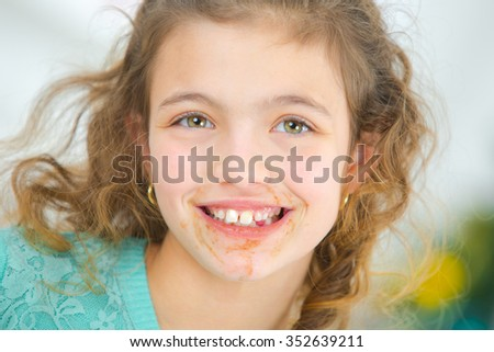 Little girl with chocolate around her mouth - stock photo