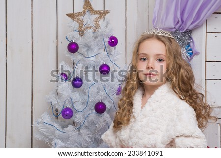 Little girl with christmas fir tree decorations - stock photo