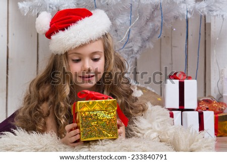 Little girl with christmas present in front of fir tree - stock photo