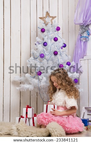 Little girl with christmas presents in front of fir tree - stock photo
