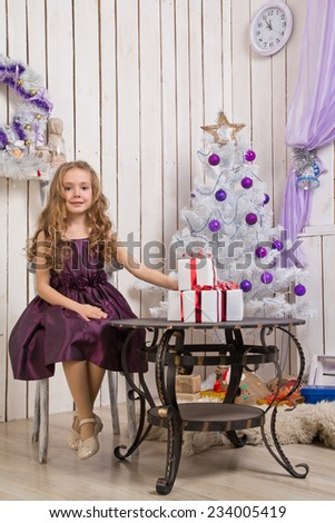 Little girl with christmas presents in front of fir tree, focus on girl - stock photo