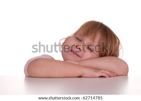 little girl with closed eyes and head on arms