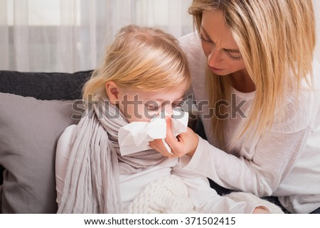 Little girl with cold and blowing her nose - stock photo