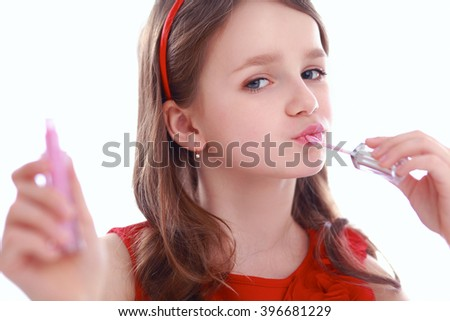 Little girl with cosmetics. Isolated on white background
