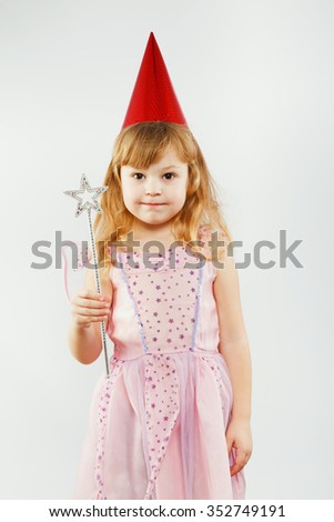Little girl, with curly blond hair, wearing on pink dress, red festal hat and fairy wings, posing with magic stick, on white background, in studio, waist up - stock photo