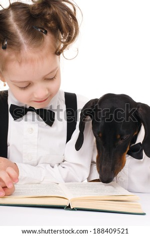 little girl with dachshund is reading a book, isolated over white - stock photo