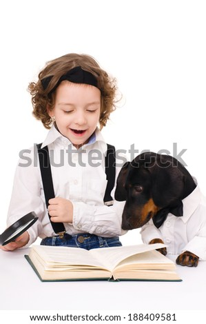 little girl with dachshund is reading a book using magnifying glass, isolated over white - stock photo