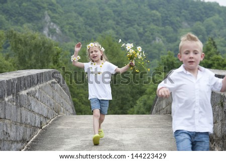 little girl with daisies in her hair, running on a bridge - stock photo