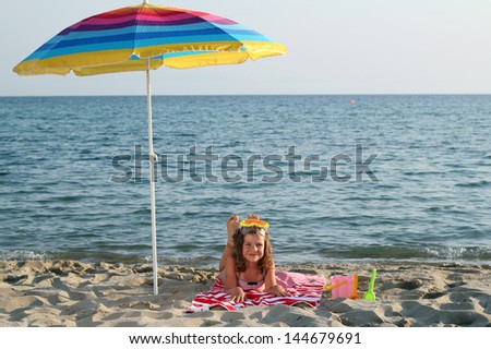little girl with diving mask lying under sunshade on beach - stock photo