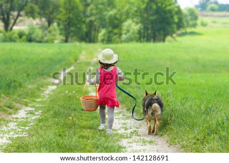 Little girl with dog going on the road to the picnic - stock photo