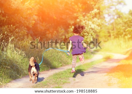 Little girl with dog running in the countryside - stock photo