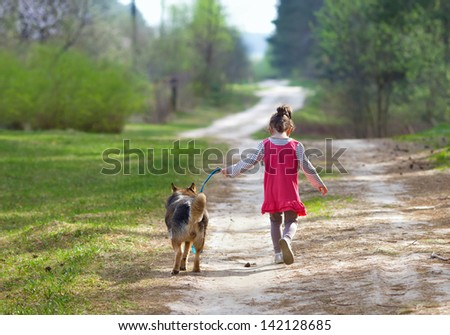 Little girl with dog running on the road - stock photo