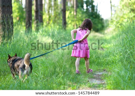 Little girl with dog running on the road in the forest