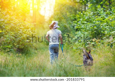 Little girl with dog walking in the forest. Back to camera. - stock photo