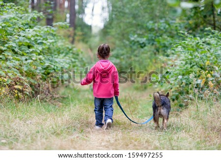 Little girl with dog walking on the road. Back to camera.