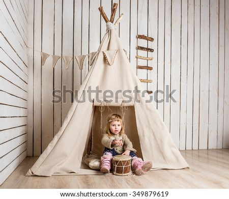 little girl with drum near wigwam playing Indian - stock photo