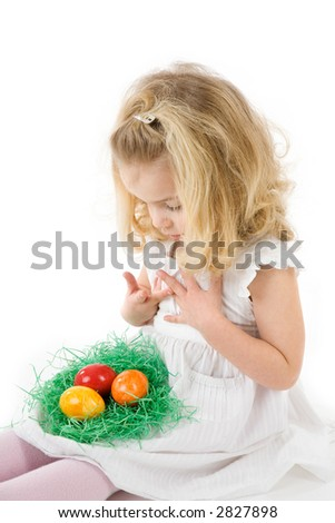 little girl with easter  eggs in a nest