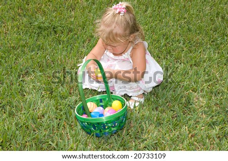 Little Girl with Easter eggs in basket - stock photo
