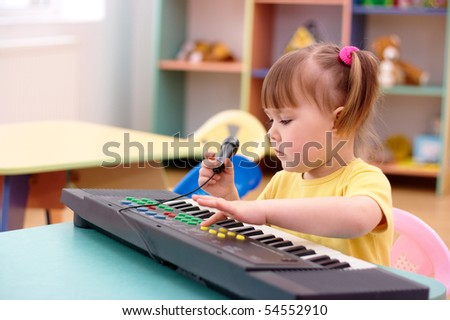 Little girl with electronic piano and microphone in preschool