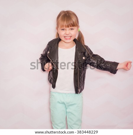 little girl with emotion on her face in a leather jacket and a white t-shirt on a light background - stock photo