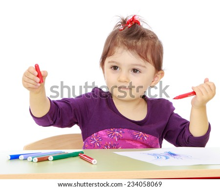 Little girl with enthusiasm draws colored markers while sitting at the table. Montessori School.Isolated on white background. - stock photo