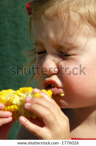 little girl with eyes shut after being sprayed by juicy corn on the cob