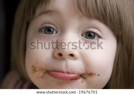 Little girl with face covered in chocolate looking at the camera - stock photo