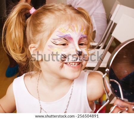 little girl with faceart on birthday party in process close up - stock photo