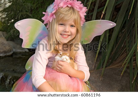 little girl with fairy wings and bunny - stock photo