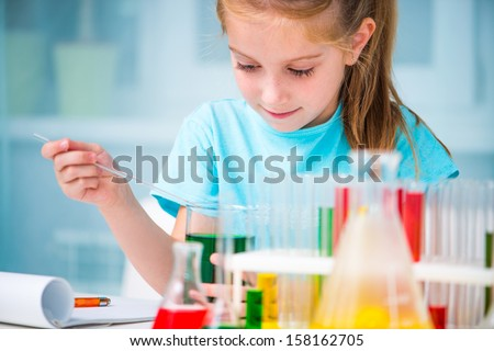 little girl with flasks for chemistry - stock photo