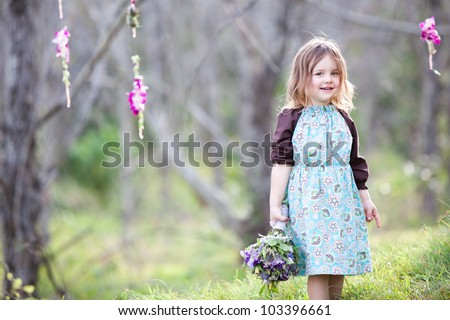 Little girl with floral bouquet in woodland - stock photo