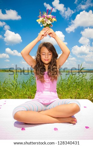 little girl with flowers and meditating in nature