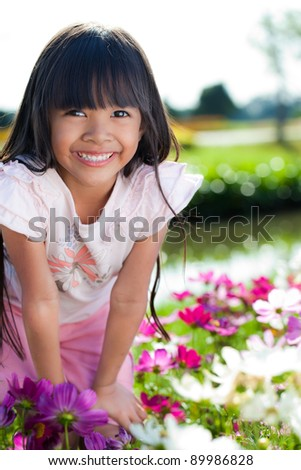 Little girl with flowers field,outdoor portrait - stock photo