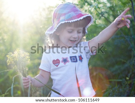 Little girl with flowers in the green grass