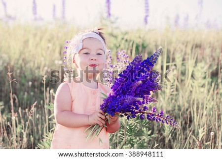 little girl with flowers outdoor - stock photo
