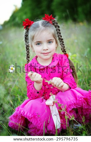 little girl with flowers outdoors - stock photo