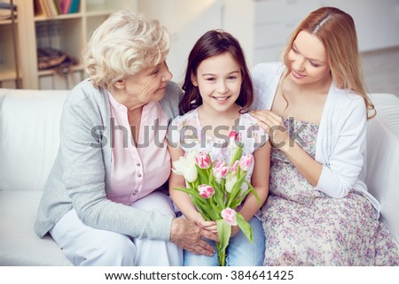 Little girl with flowers sitting with her family on the sofa - stock photo