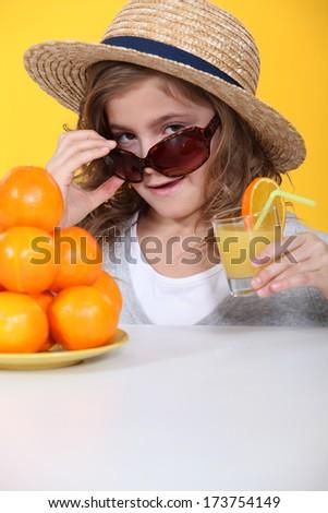 Little girl with freshly squeezed orange juice - stock photo