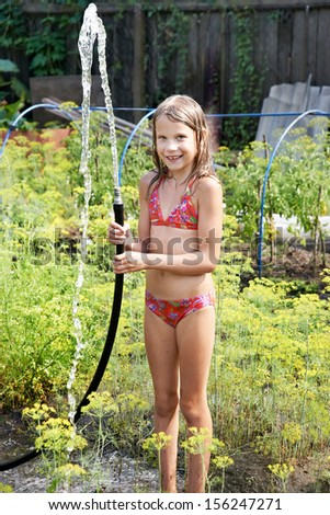 Little girl with garden hose and water