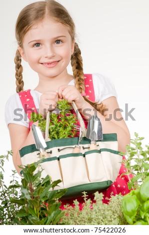 Little girl with gardening tools in herbal garden - stock photo