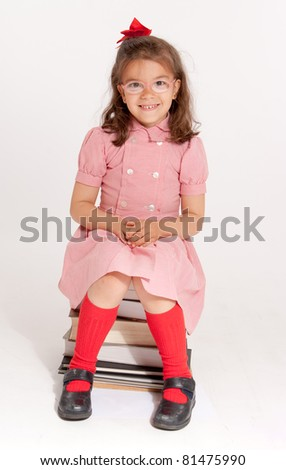 Little girl with glasses and a happy funny expression sitting on a pile of books
