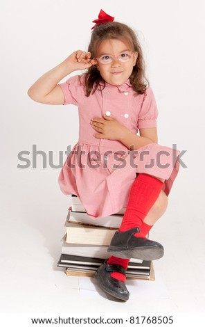 Little girl with glasses and a happy funny expression sitting on a pile of books - stock photo