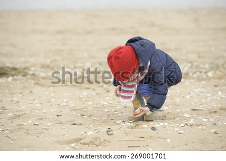 little girl with glasses playing on the beach  - stock photo