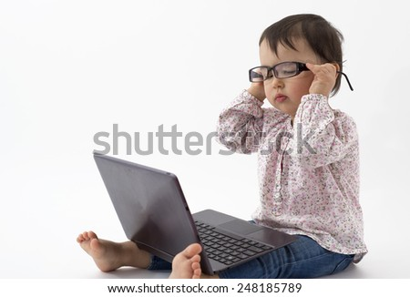Little girl with glasses watching on the notebook - stock photo