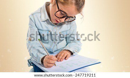 Little girl with glasses writing - stock photo