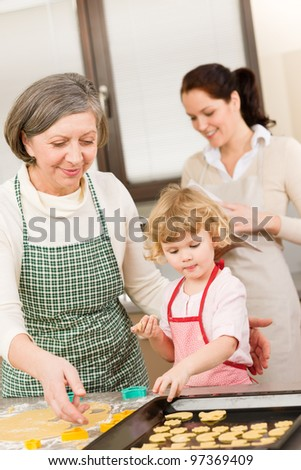 Little girl with grandmother baking cookies put on tray - stock photo